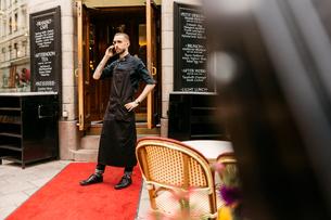 Baker on phone outside bakery in Swedenの写真素材 [FYI02207724]