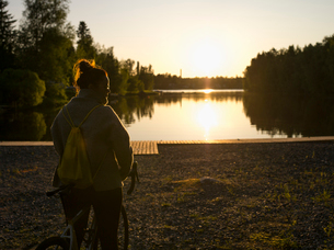 Finland, Ostrobothnia, Jakobsta, Silhouette of woman standing by river at sunsetの写真素材 [FYI02207736]