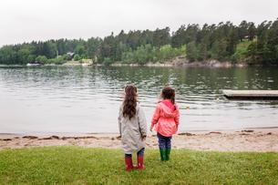 Sweden, Uppland, Roslagen, Vato, Two girls (4-5, 6-7) standing by lake shoreの写真素材 [FYI02207740]