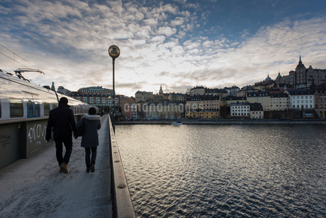 Rear view of couple walking at waterfront in Stockholm, Swedenの写真素材 [FYI02207765]