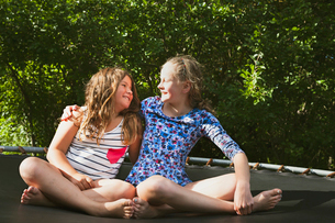Sweden, Oland, Two girls (8-9, 10-11) embracing on sunny dayの写真素材 [FYI02207775]