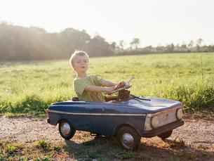 Boy sitting in toy carの写真素材 [FYI02207820]