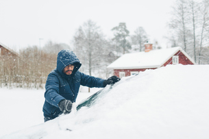 Man clearing snow from his carの写真素材 [FYI02207829]