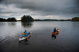 Sweden, Smaland, Mature men in boats on lake surrounded by forestの写真素材 [FYI02207858]