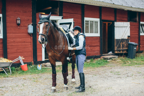 Sweden, Blekinge, Mid adult woman and horse in front of stableの写真素材 [FYI02207863]