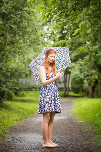 Finland, Pirkanmaa, Tampere, Woman wearing floral dress standing with umbrella in parkの写真素材 [FYI02207865]