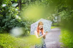 Finland, Pirkanmaa, Tampere, Woman wearing floral dress standing with umbrella in parkの写真素材 [FYI02207888]