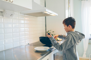 A young boy in the kitchen cookingの写真素材 [FYI02207921]