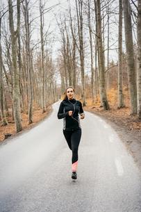 Young woman running on rural road in Sodermanland, Swedenの写真素材 [FYI02207943]