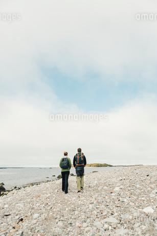Rear view of couple walking along rocky coastline in Stockholm, Swedenの写真素材 [FYI02207968]