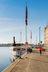 Sweden, Stockholm, Nybroviken, Rear view of man running in harborの写真素材 [FYI02207982]