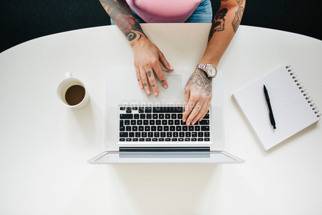 Tattooed woman using a laptop in Stockholmの写真素材 [FYI02207985]