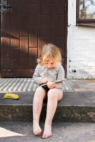 Sweden, Skane, Girl (4-5) sitting on steps and using tabletの写真素材 [FYI02208023]