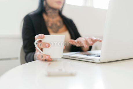 Tattooed woman holding a mug while using a laptopの写真素材 [FYI02208025]