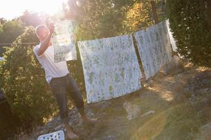 Sweden, Stockholm Archipelago, Sodermanland, Orno, Mature man hanging sheet on laundry lineの写真素材 [FYI02208045]