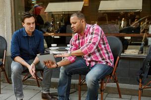Sweden, Mature men looking at digital tablet in sidewalk cafeの写真素材 [FYI02208085]