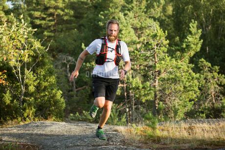 Man running through a forest in in Akersberga, Swedenの写真素材 [FYI02208115]