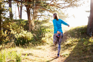 Woman stretching on forest path at Sandhammeren, Swedenの写真素材 [FYI02208116]