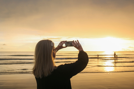 Woman taking photograph of beach during sunset in Ko Lanta, Thailandの写真素材 [FYI02208122]