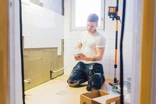 Man tiling a wallの写真素材 [FYI02208125]