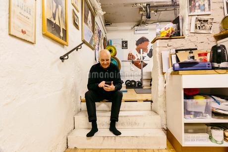 Senior man using smart phone in boxing gymの写真素材 [FYI02208132]
