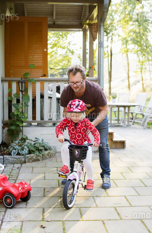 Man teaching his daughter to ride bicycle in Swedenの写真素材 [FYI02208177]