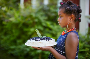 Girl holding cake with blueberriesの写真素材 [FYI02208184]