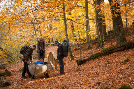 Men carrying kayak through forest in Blekinge, Swedenの写真素材 [FYI02208187]