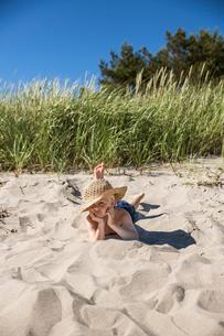 Sweden, Gotland, Boy (6-7) in straw hat lying on beachの写真素材 [FYI02208190]