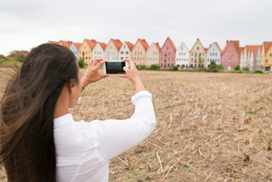 Sweden, Skane, Jakriborg, Woman photographing colorful townhousesの写真素材 [FYI02208216]