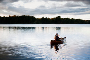 Sweden, Smaland, Mature man in boat on lake surrounded by forestの写真素材 [FYI02208228]