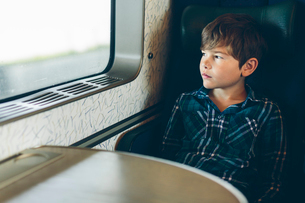 A young boy travelling on a trainの写真素材 [FYI02208251]