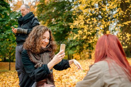Sweden, Vastergotland, Gothenburg, People using mobile phones in parkの写真素材 [FYI02208281]