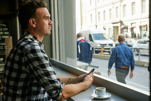 Sweden, Man holding cellphone and looking through window in cafeの写真素材 [FYI02208287]