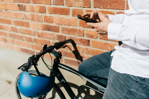 Man on bicycle texting in Swedenの写真素材 [FYI02208294]