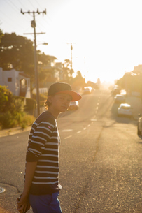 USA, California, Pacific Grove, Boy (14-15) standing on suburban roadの写真素材 [FYI02208345]