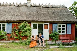Family sitting on steps in Friseboda, Swedenの写真素材 [FYI02208354]