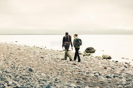 Rear view of couple walking along rocky coastline in Stockholm, Swedenの写真素材 [FYI02208383]