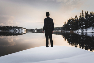 Rear view of man by lake in snow in Sodermanland, Swedenの写真素材 [FYI02208388]