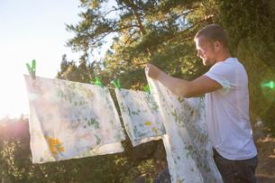 Sweden, Stockholm Archipelago, Sodermanland, Orno, Mature man hanging sheet on laundry lineの写真素材 [FYI02208420]