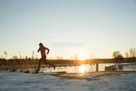 Silhouette of woman jogging by lake at sunsetの写真素材 [FYI02208438]