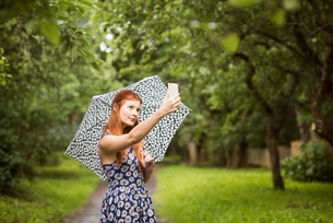 Finland, Pirkanmaa, Tampere, Woman wearing floral dress standing with umbrella in park and taking seの写真素材 [FYI02208469]