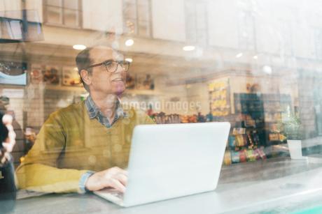Man using a laptop behind a windowの写真素材 [FYI02208477]