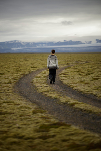 Iceland, Sudurland, Hiker on dirt road through wilderness towards mountain range on horizonの写真素材 [FYI02208491]