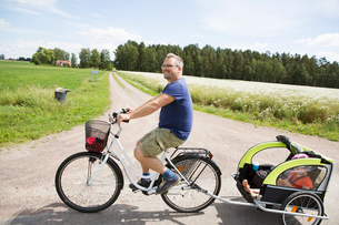 Man cycling with his daughter in Smaland, Swedenの写真素材 [FYI02208495]
