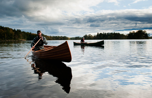 Sweden, Smaland, Mature men in boats on lake surrounded by forestの写真素材 [FYI02208496]