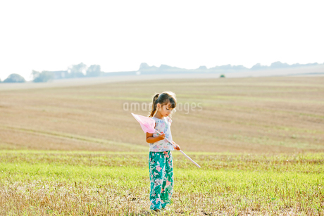 Girl with bug net in field in Friseboda, Swedenの写真素材 [FYI02208511]