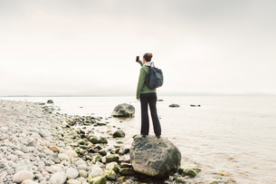 Woman holding up phone on rocky coastline of Sodermanland, Swedenの写真素材 [FYI02208539]