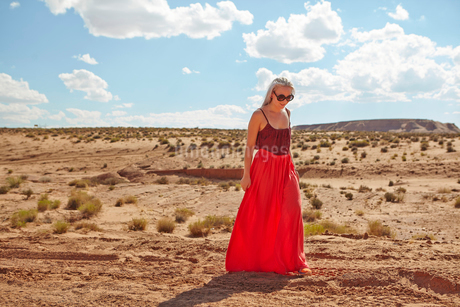 USA, Arizona, Young blonde woman wearing red skirt walking in desertの写真素材 [FYI02208543]