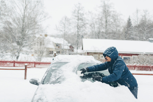 Man clearing snow from his carの写真素材 [FYI02208544]